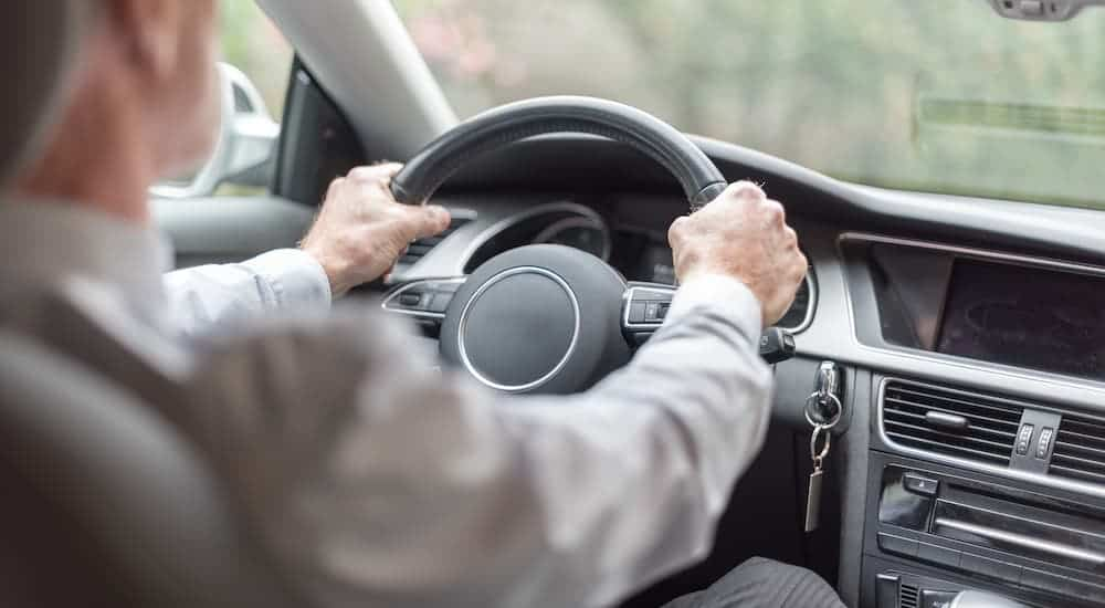 An older man is shown driving a car and gripping the steering wheel.