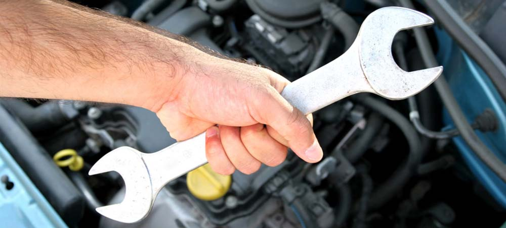 Wrench being held in front of engine