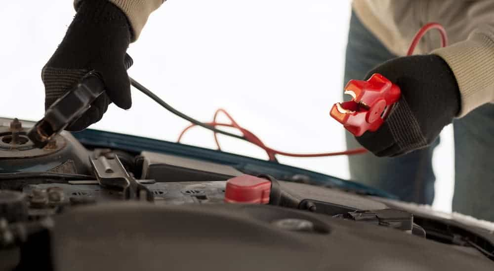 Gloved hands are attaching jumper cables to a car battery in the winter in Cincinnati, OH.