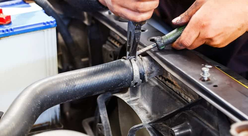 A mechanic is replacing a coolent hose in a car.