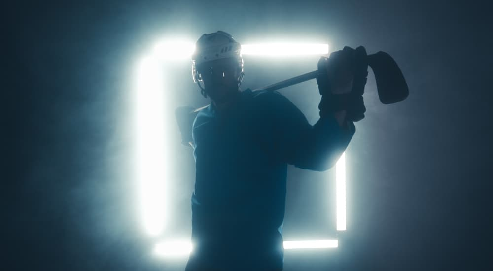 A black silhouette of a hockey player in front of a square light