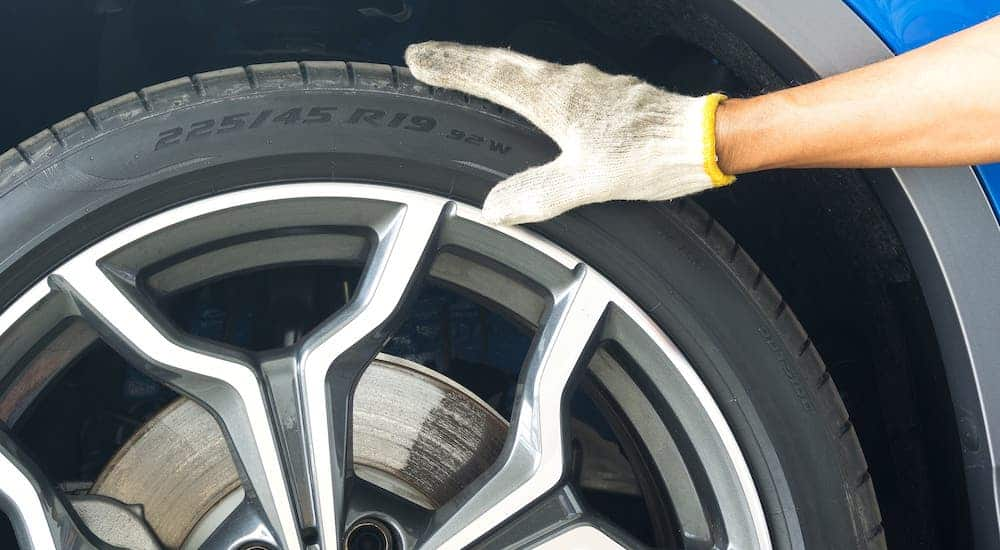 A gloved hand is on a tire.