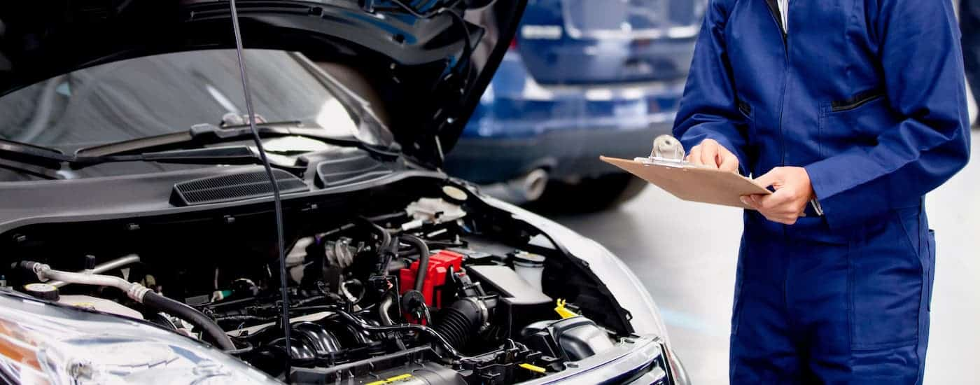 A mechanic with a clipboard is inspecting a car's engine.